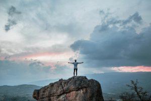 Mann steht auf Felsen mit ausgebreiteten Armen und geht seinen erfolgreichen Weg