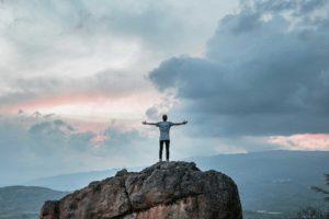 Mann auf Felsen schaut in Himmel mit ausgebreiteten Armen